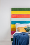 Close-up of a rainbow painting standing against white wall, behind a cozy bed in white bedroom interior. Real photo