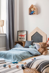 Plush toy next to blue bed with pillows in kid's bedroom interior with fox poster and doll. Real photo