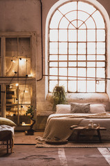 Lights on wooden cabinet in bright loft bedroom interior with window above bed with pillows. Real photo