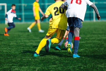Boys at white yellow sportswear run, dribble, attack on football field. Young Soccer players with ball on green grass. Training, football, active lifestyle for kids