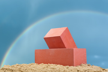 Two red ceramic bricks on the sand at the dark blue sky background with rainbow © Evgesha