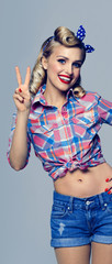 woman, showing two fingers or victory gesture, dressed in pin-up style © vgstudio