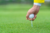 Hand caddy hold Golf ball with tee ready to be shot at golf court