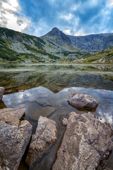beauty day landscape on the mountain lake with rocks at the front. Vertical view © EdVal