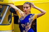 portrait indian beautiful Caucasian woman in traditional blue dress.hindu model with golden kundan jewelry set bindi earrings and nose ring piercing nath fashion photoshoot on srilankan street market