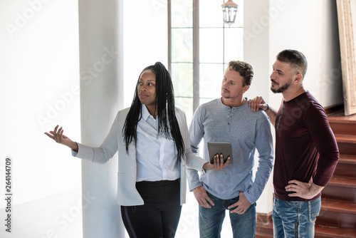 Gay couple with African American female real estate agent in new house © kritchanut