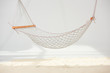 hanging hammock made of net over sand on grey