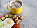 Sandwich with fried egg, nuts, dried apricots and cucumber and a Cup of coffee on a concrete background