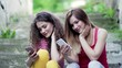 Young teenage female friends sitting outdoors in town, using smartphone.