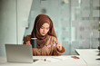 Islam woman working with laptop and holding a coffee mug and glasses.