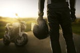 Motorradfahrer steht vor seinem Motorrad im Sonnenuntergang