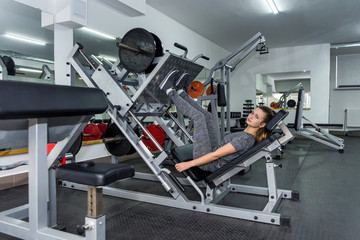 Woman is working on quadriceps in the gym