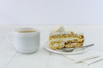 Cup of coffee and piece of cake on wooden table