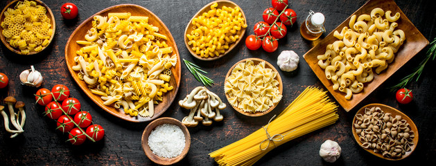 Assortment of different types of raw pasta with mushrooms, tomatoes and garlic. © OlesyaSH