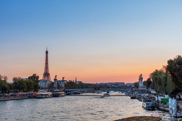 Sunset view of Eiffel tower, Alexander III and Seine river in Paris, France. Architecture and landmarks of Paris.