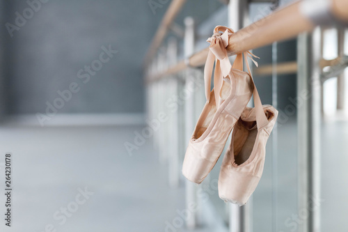 Pointe shoes hang on ballet barre in dance class room. Blurred background of ballet classic school. © Marina Andrejchenko