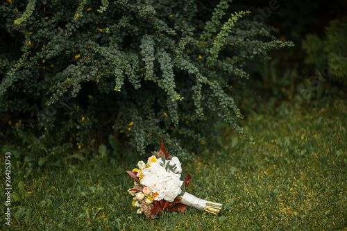 Beautifully decorated bride's bouquet of different flowers and green leaves lies on the green grass near the Bush. Wedding theme. © Sanborr
