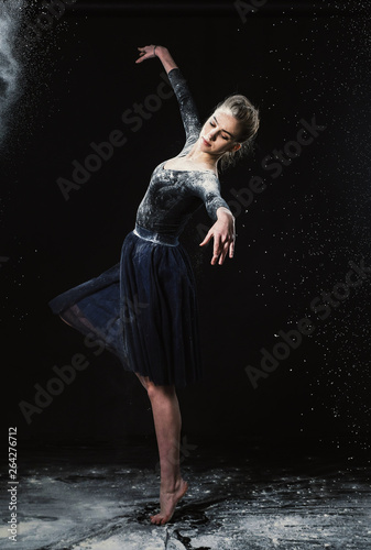 A young beautiful girl in a swimsuit and a translucent skirt emotionally dancing on a black background in clouds of white dust © Антон Фрунзе