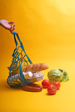 products, fruits, vegetables, bread in a shopping bag on a yellow background