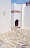 Beautiful Greek architecture, white walls, blue sky, narrow street and perfect geometry of shapes