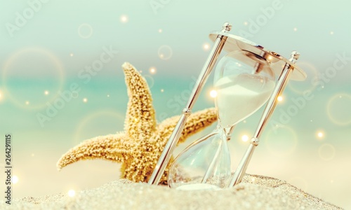 Hourglass and seastar on sandy beach