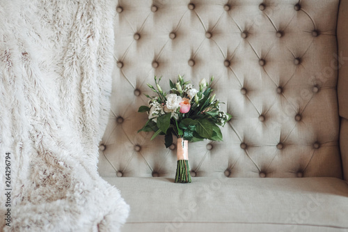 Wedding bouquet of flowers lying on the gray sofa next to the white fur coat in the studio. Wedding details. The bride's bouquet.