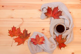 Mug of hot coffee, wrapped in scarf and colorful autumn maple leaves on wooden background.
