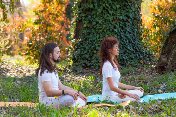 young man and woman practice yoga meditation in nature side view full body shot in wood