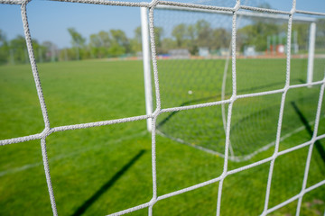 Empty football playground. Soccer football net and blurry stadium. Close up detail of a soccer net Football soccer field. Hang bended white