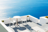 Two chairs with table on the terrace overlooking the sea. Santorini island, Greece.