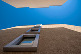interesting architecture with windows in a line to the top and blue sky in a gorge of houses