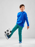 childhood, football and sport concept - smiling boy in blue hoodie playing soccer ball over grey background