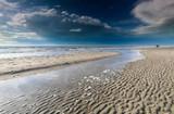 couple walking on sunny North sea beach
