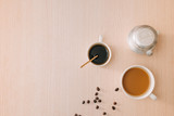 Cups of coffee with coffee beans and vietnamese Phin filter on wooden background