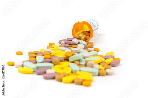 Pile of multicolored pills in front of prescription bottles