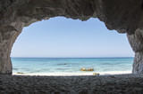 View on turquoise sea through a stone cave in Kefalonia island, Greece