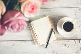roses with coffee and notepad on desk