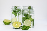 Healthy refreshing drink with ice, lime and mint isolated on white background.
