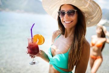 Happy beautiful woman drinking cocktails during summer vacation on beach