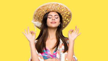 Teenager girl on summer vacation in zen pose over isolated yellow background