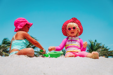 cute little girls play with sand on beach