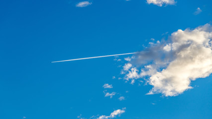 Aircraft at the blue sky, condensation trail