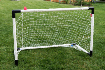 The small goal for the soccer on the green field in the garden