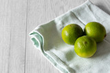 Lime on a pastel green tea towel with a grey wood background