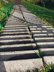 concrete staircase on a steep slope of green grass © makam1969