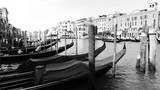 Water canal in Venezia or Venice, Italy with buildings and gondolas black and white