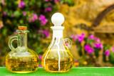 Virgin olive oil in two vintage oil bottles, outdoor.