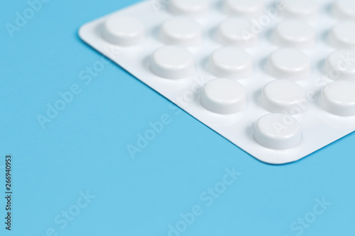 Close-up photo white blister of pills on blue background. Medical, pharmacy and healthcare concept.