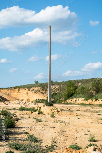old electrical post in the middle of sand quarry